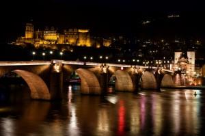 Blick vom Neckarufer auf das nächtliche Heidelberg